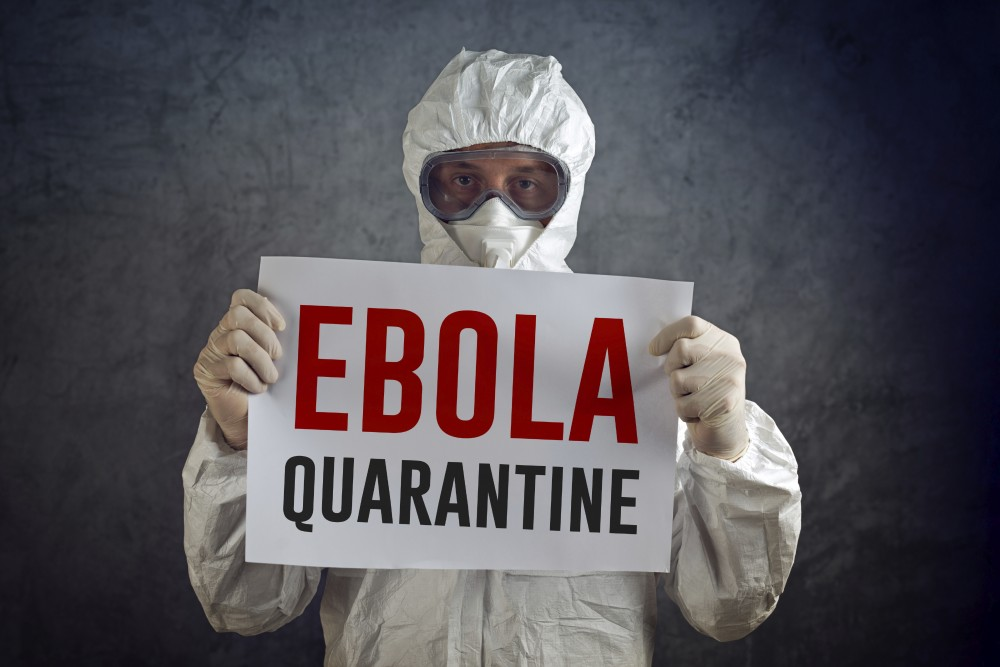 Ebola Quarantine sign held by medical healh care worker wearing protective gown, glowes, mask and goggles.