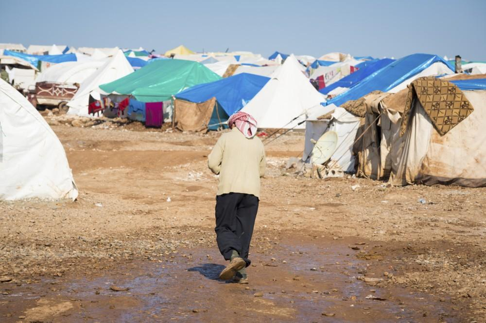 A Syrian refugee walks at the camp for internally displaced persons in Atmeh, Syria, adjacent to the Turkish border