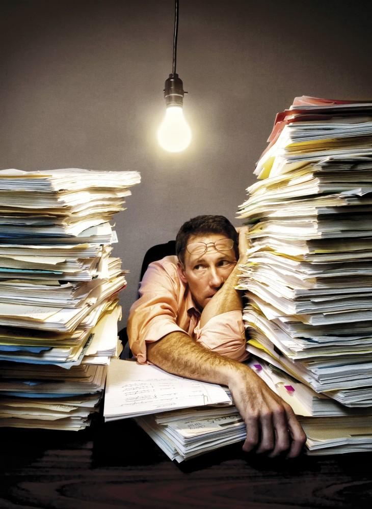 Overwroked businessman resting with stacks of documents on desk.