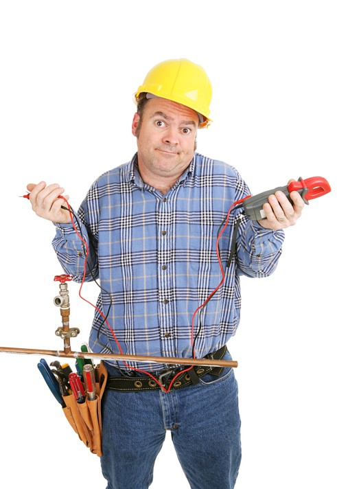 Electrician confused by a plumbing project.  Hes holding a voltage meter which is useless on a plumbing pipe.  Isolated on white.