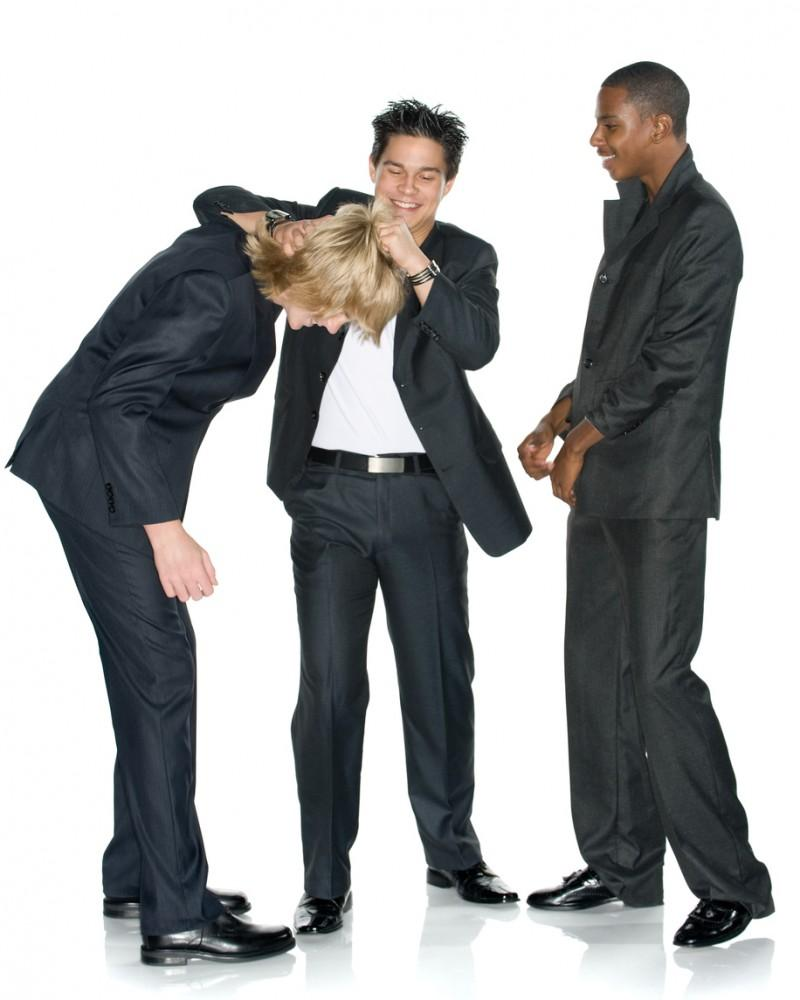 Fun, light, and lively image of three young business men. Asian American man is giving a noogie to the new guy. Studio shot. Isolated on white.