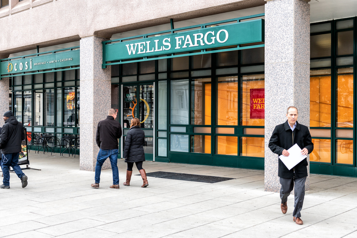 Washington DC, USA - March 9, 2018: Wells Fargo bank branch entrance, facade, building, windows, many people walking on sidewalk street in capital city, business, businessman holding document