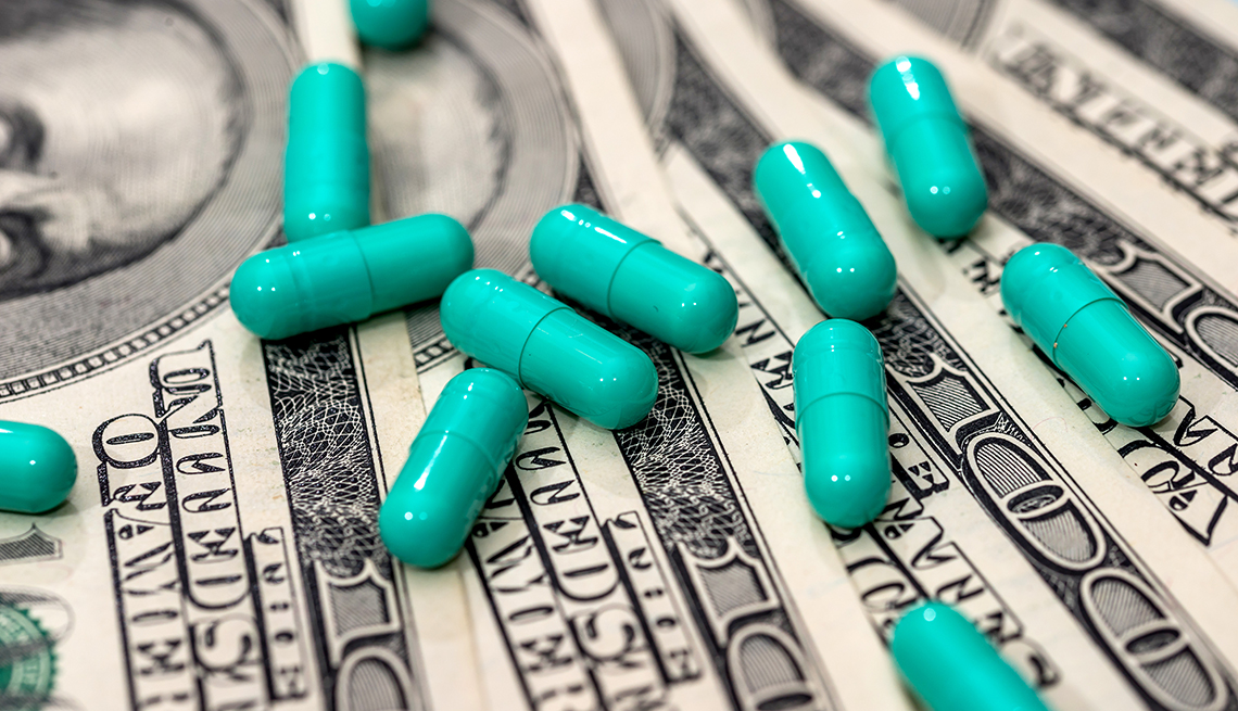 Medicines capsules on dollar bills close up