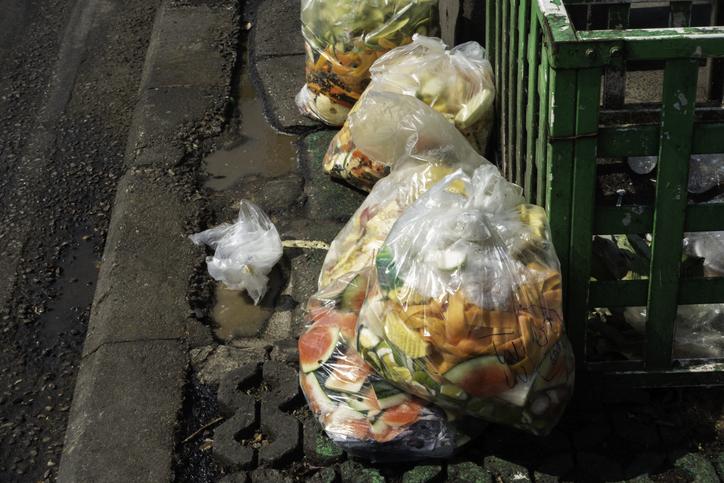 Food waste in plastic bags on footpath