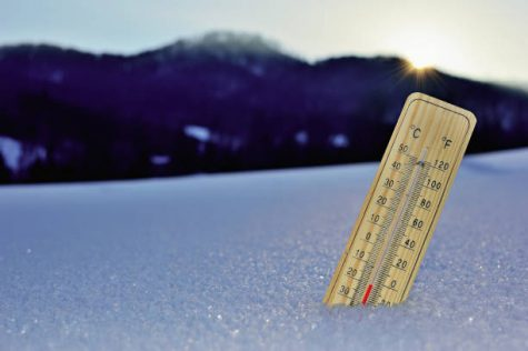 Mercury wooden thermometer stuck on snow shows very low temperatures. Temperatures in Celsius and Fahrenheit degrees. Cold winter weather. Twenty degrees under zero during the day.