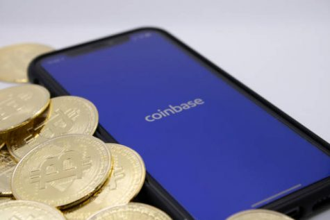 Bitcoins placed beside Coinbase App on iPhone, illustrating one of the largest Bitcoin providers, photographed in Cologne, Germany, 14th of April 2021